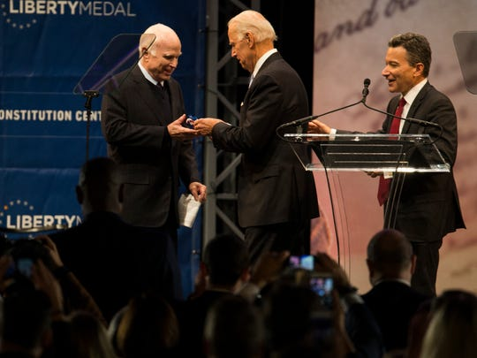 Former Vice President Joe Biden, center, awards Sen. John McCain, left, with the 2017 Liberty Medal during the 29th annual Liberty Medal Ceremony Monday in Philadelphia, Pa.
