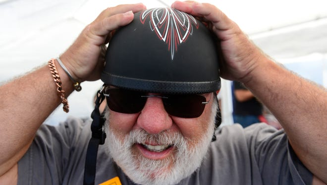 David Yohe, of Hanover, tries on one of the motorcycle helmets for sale at the 929 Customs stand during the Harley-Davidson open house on Thursday. The event continues on both Friday and Saturday from 9 a.m. until 4 p.m.