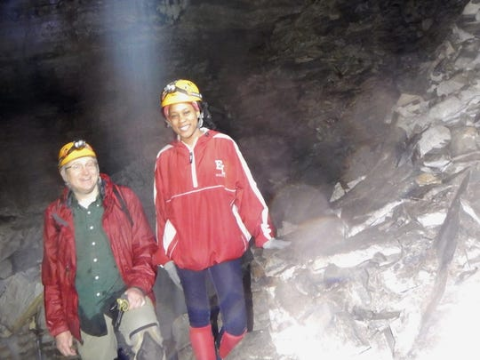Graduate student JeTara Brown and Dr. Tom Byl collect samples from a waterfall in Mammoth Cave during a rainfall event.