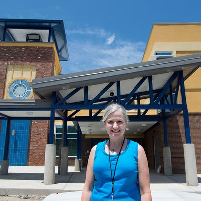 Carleene Finger, principal of the new Enka Middle School, stands in the stairwell admiring the nearly-finished building July 19, 2016. The $25 million school will open this fall with fifth and sixth graders from Pisgah, Candler, Sand Hill-Venable and Hominy Valley elementary schools.