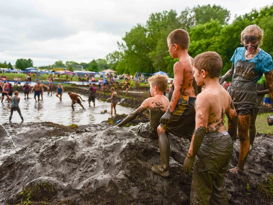 "Kids stand on what they call ""Mud Mountain"" and watch the adults play mud volleyball on Saturday, August 29, 2015, during Altoona Palooza at  Sam Wise Youth Complex."