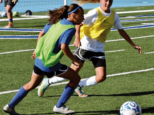 Matt Hollinshead — Current-Argus Eighth grade midfielder Baylee Molina looks to pass the ball toward the back line against freshman defender Jensen Leivo at Tuesday's practice.