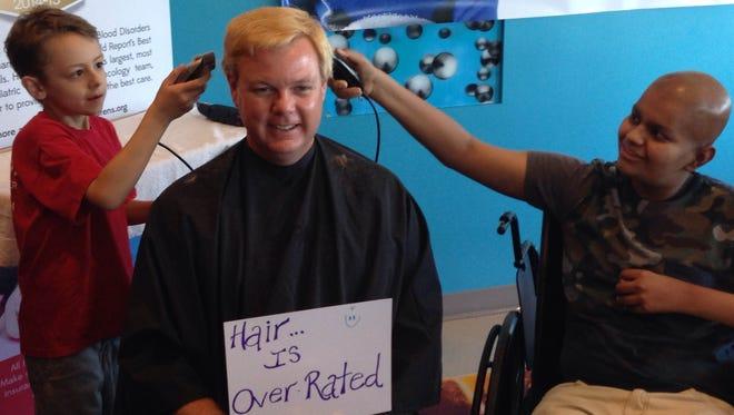 Ori Wright, left, shaves Chris Oless's hair at Phoenix Children's Hospital Tuesday.