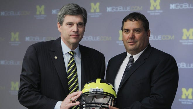 University of Michigan athletic director Dave Brandon, left, stands with then new football coach Brady Hoke at a news conference in Ann Arbor, Mich.