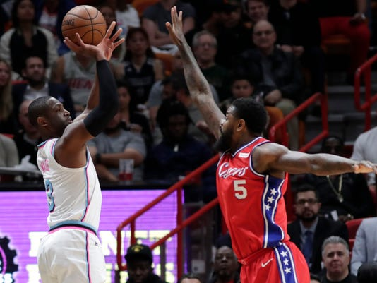 Miami Heat's Dwyane Wade, left, shoots a 3-point basket over Philadelphia 76ers' Amir Johnson (5) during the first half of an NBA basketball game Thursday, March 8, 2018, in Miami. (AP Photo/Lynne Sladky)