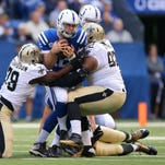 Indianapolis Colts quarterback Andrew Luck (12) looses 15-yards on a sack during the second half of an NFL football game Sunday, Oct. 25, 2015, at Lucas Oil Stadium.