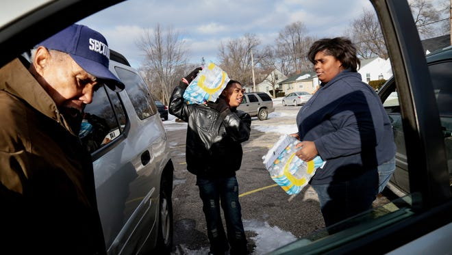 Members of Citi Praise Church in Detroit, Damion Allen, 13, center, and Jasmine Crawford, 25, helps carry cases of bottled water to Leroy Davis, 77, of Flint, MI, during the Rally For Justice at the Heavenly Host Gospel Baptist Church on Sunday, Jan. 17, 2016 in Flint, MI. Salwan Georges/Special to the Detroit Free Pres