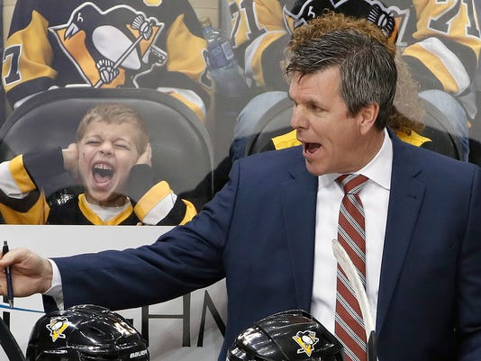 Pittsburgh Penguins head coach Mike Sullivan, right, gives instructions as a young fan reacts during the overtime period of an NHL hockey game against the New York Islanders in Pittsburgh, Saturday, March 3, 2018. (AP Photo/Gene J. Puskar)