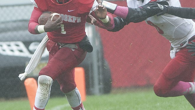 St. Joseph quarterback Salaam Horne, pictured here trying to break away from Vineland's Nihym Anderson earlier this season, scored four touchdowns last week.
