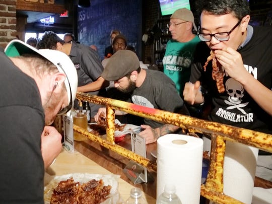 Journal & Courier reporter Wei-Huan Chen, right, takes on Todd Dotson, left, and others at the pop-up two-pound bacon challenge Aug. 8 at DT Kirby's in Lafayette. Todd Dotson won the event and was crowned champion after eating all 2 pounds.