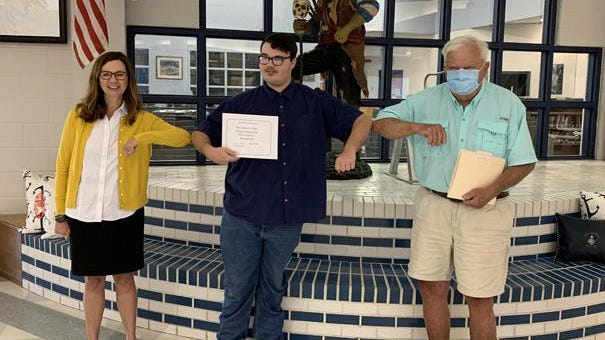 Swansboro High School graduate Michael Diaz is the 2020 recipient of the Joseph G. Plasky Robotics Scholarship, which rewards students who use their experience as members of the SHS Robotics Club to pursue STEM-related careers. The scholarship was recently awarded at the school by Plasky, a retired DuPont engineer and long-time mentor for the Robotics Club. Pictured are Swansboro High School principal Helen Gross, Diaz, and Plasky.