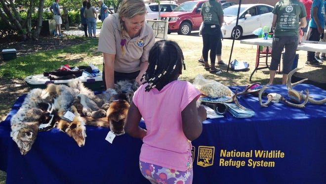 Tina Chouinard of the U.S. Fish and Wildlife Service teaches young children about different animals Saturday at the Earth Day Festival.