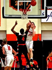 Anderson center Hunter Bode rejects the shot of Withrow forward Dominic Johnson in the game between the Withrow Tigers and the Anderson Redskins at Anderson High School.