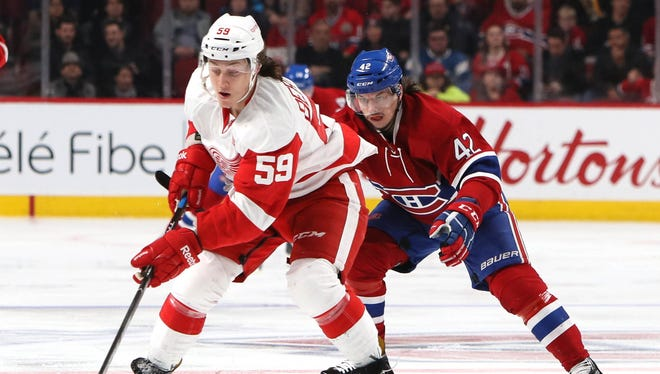 Red Wings left wing Tyler Bertuzzi (59) plays the puck against Canadiens right wing Sven Andrighetto (42) during the second period of the Wings' 5-0 loss Saturday in Montreal.