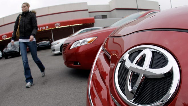 A customer walks past a  Toyota Camry at a dealership in Nashville, Tenn. in this 2010 file photo.
