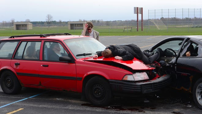 Student actors portray the aftermath of a car wreck during a mock car crash at Two Rivers High School on Wednesday. The event, which also included a mock funeral, aimed to educate students on the dangers of drinking and driving.