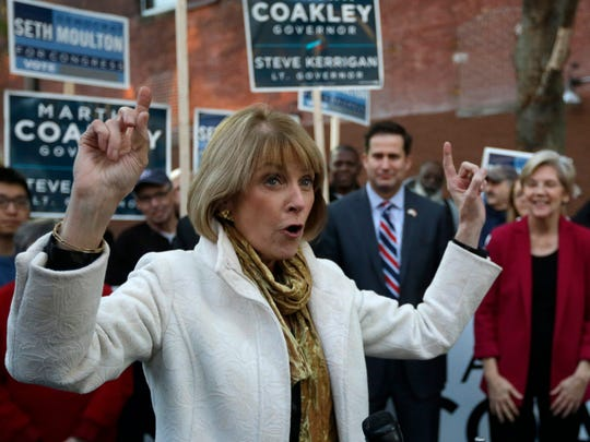 Massachusetts Democratic gubernatorial candidate Martha Coakley, left, raises her arms while speaking to a crowd as U.S. Sen Elizabeth Warren, D-Mass., right, and Democrat Seth Moulton, a candidate for the U.S. House of Representatives, second from right, look on during a Monday, Nov. 3,  2014, campaign event in Lynn, Mass.