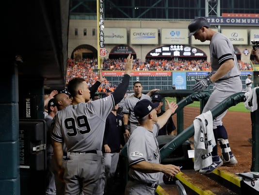 New York Yankees' Greg Bird is congratulated after hitting a home run during the ninth inning of Game 1 of baseball's American League Championship Series against the Houston Astros Friday, Oct. 13, 2017, in Houston. (AP Photo/David J. Phillip)