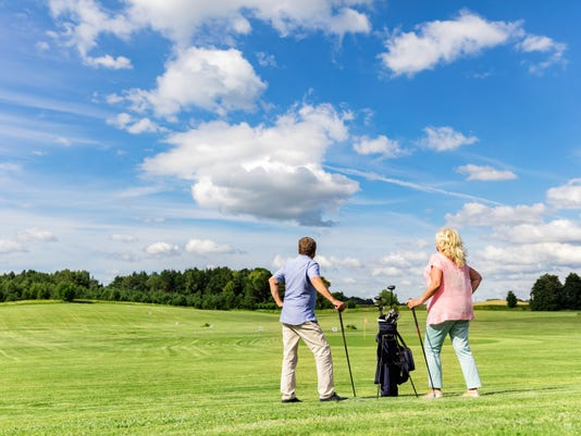 Active senior couple playing golf on a course.