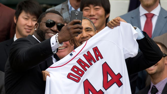 "Boston Red Sox player David ""Big Papi"" Ortiz takes a selfie with President Barack Obama, holding a Boston Red Sox jersey presented to the president during a ceremony on the South Lawn of the White House in Washington today where the president honored the 2013 World Series baseball champion Boston Red Sox. In the background are pitchers Junichi Tazawa, left, Koji Uehara, right."