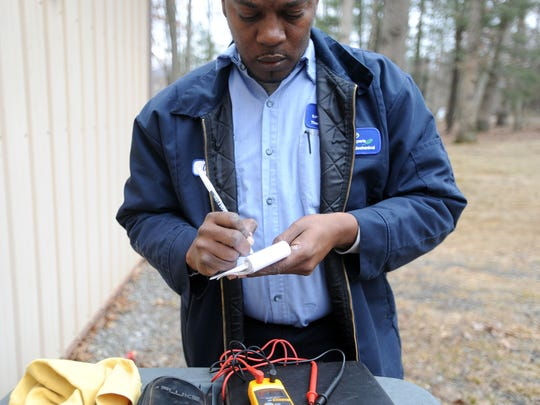 Technician Daniel Allen jots down notes regarding an air conditioning unit in Fletcher on Monday. Allen works at Thompson Mechanical Heating and Cooling and is scheduled to graduate from Asheville-Buncombe Technical Community College in May.