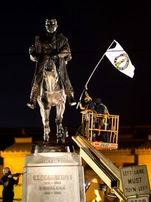 A worker in protective gear takes down an Army National Guard flag from the statue of Confederate General P.G.T. Beauregard during the statue's removal from the entrance to City Park in New Orleans, Tuesday, May 16, 2017.