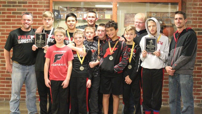 Fairview Middle School Falcon wrestlers placing at the MCAC tournament proudly display their medals and Third Place team plaque. Riley Bennett (with hood) displays his Most Valuable Wrestler plaque.