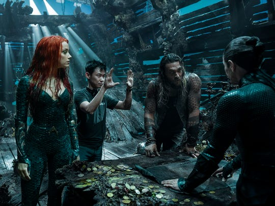 "Director James Wan (center) goes over a scene with Amber Heard and Jason Momoa on the set of ""Aquaman."""