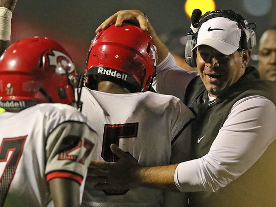 Clinton High coach Judd Boswell, right congratulates Desmyn Baker (5) after he scored a touchdown during the first half of a high school football game against Starkville High in Starkville, Miss., Friday, Nov. 3, 2017.  (Jim Lytle/Special to the Clarion Ledger)
