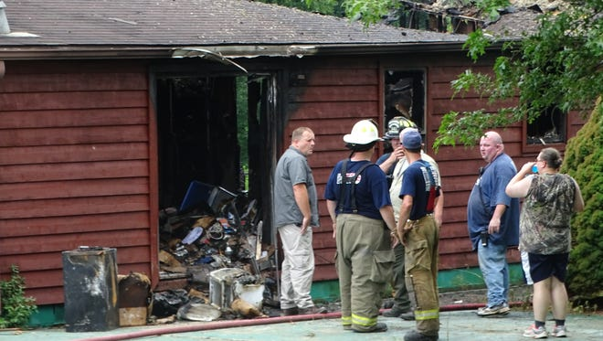 Fire officials discuss the next steps in determining the cause of a fire that gutted a home at 433 Smith Lane near Londonderry Thursday morning.