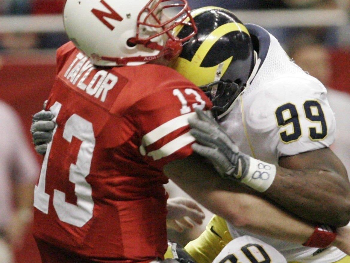 A mouthpiece pops free as Michigan's Alan Branch (80) and Pierre Woods (99) drill Nebraska quarterback Zac Taylor in the 2005 Alamo Bowl.