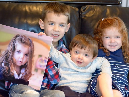 Brooke Healey's brothers and sister - Ashton, 7, Seamus (middle) 1 and Bryn, 4, hold her picture
