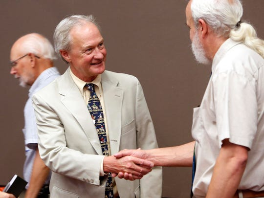 Democratic presidential candidate former Rhode Island Gov. Lincoln Chafee shakes hands as he meets Belknap County Democrats during a campaign stop in Laconia, N.H., on June 24, 2015.