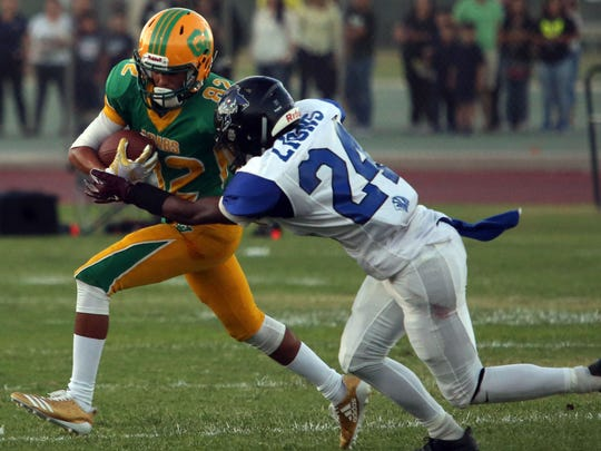 Coachella Valley's Johnny Ortiz carries the ball for a gain as Cathedral City's James Green III tries to tackle him on Friday, August 25, 2017 in Thermal.