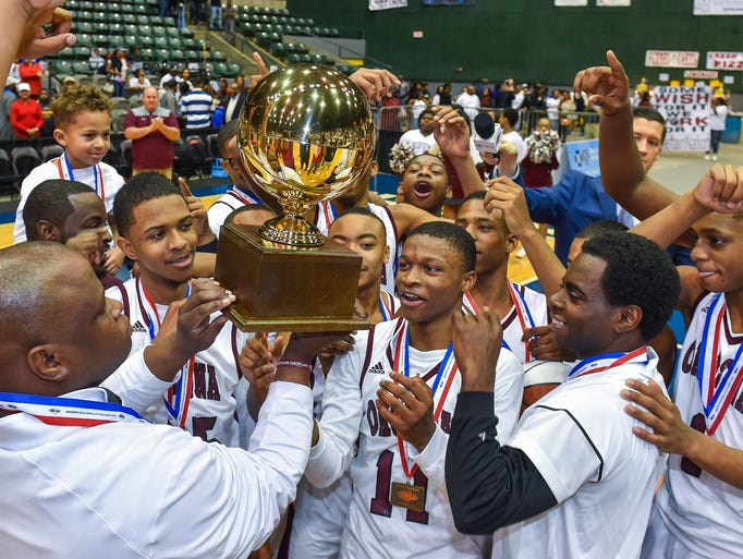 Okolona coach Arteria Clifton hoists the trophy and