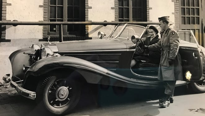 Reporter Sue Mellett, behind the wheel of a Hitler car, with 1st Lt. James C. Cox, at the Cadle Tabernacle, November 1945