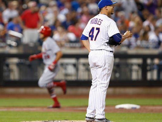 New York Mets relief pitcher Hansel Robles (47) smiles as he watches a video replay on a giant screen in center field after allowing a three-run home run to St. Louis Cardinals' Tommy Pham, left, during the sixth inning of a baseball game Monday, July 17, 2017, in New York. (AP Photo/Kathy Willens)