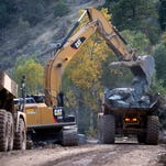 Reconstruction of CR 27 along Buckhorn Creek is underway Monday, Sept. 15, 2014 where portions of the road were destroyed in the September 2013 flood. Most of the road is being moved further back from the creek and the banks armored with rock to protect against erosion.