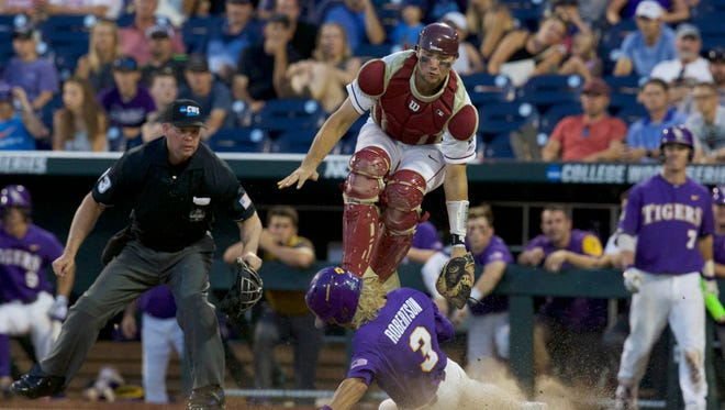 LSU shortstop Kramer Robertson (3) scores a run under Florida State catcher Cal Raleigh (35) in the ninth inning at TD Ameritrade Park Omaha.