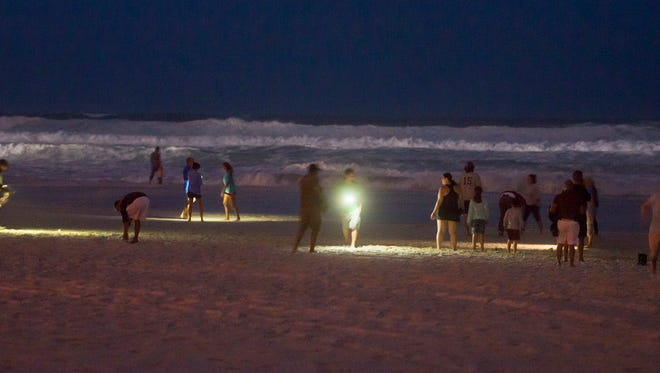 Sightseers take photos of the high surf as Hurricane Nate approaches in Pensacola Beach during twilight on Saturday, October 7, 2017.