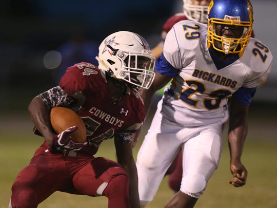Madison County running back Derrick Staten tries to break away from Rickards' Dezmone Williams during their season-opening game.