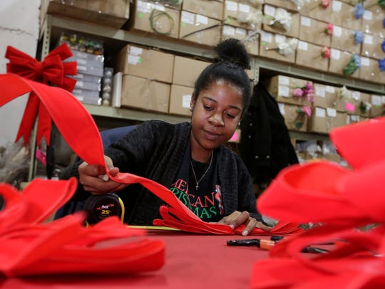 Brianna Edwards makes bows at the American Christmas