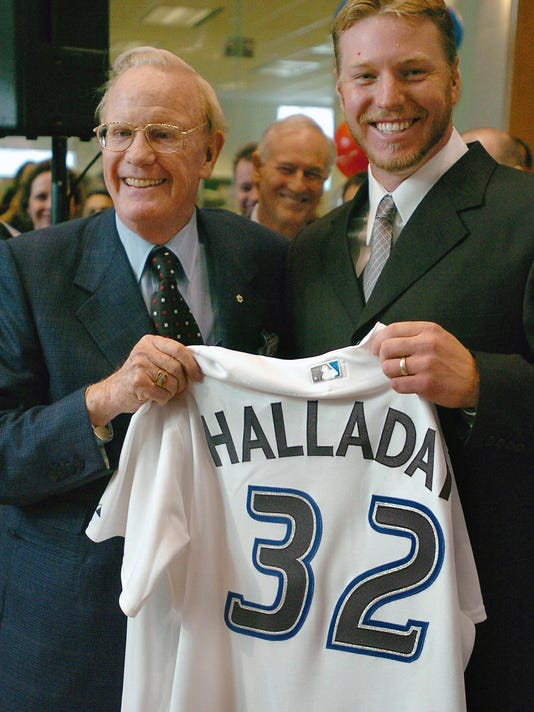 FILE - In this Jan. 22, 2004, file photo, Toronto Blue Jays pitcher Roy Halladay, right, and Rogers Communications Inc. president and CEO Ted Rogers smile during a press conference in Toronto, after Halladay signed a four year, $42 million contract with the Blue Jays. Roy Halladay's No. 32 will be retired by the Toronto Blue Jays before their opener against the New York Yankees on March 29. Halladay died at age 40 on Nov. 7 when the plane he was piloting crashed into the Gulf of Mexico. Toronto will wear a No. 32 patch on its uniforms this season. (Aaron Harris/The Canadian Press via AP, File)
