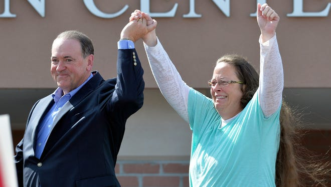 In this Sept. 8, 2015, file photo, Rowan County Clerk Kim Davis, with Republican presidential candidate Mike Huckabee at her side, greets the crowd after being released from the Carter County Detention Center, in Grayson, Ky. Davis, hauled to jail for defying a series of federal court orders and refusing to issue marriage licenses to same-sex couples, filed a 40-page court document Thursday, Sept. 24, blaming Kentucky governor Steve Beshear for all her legal woes.