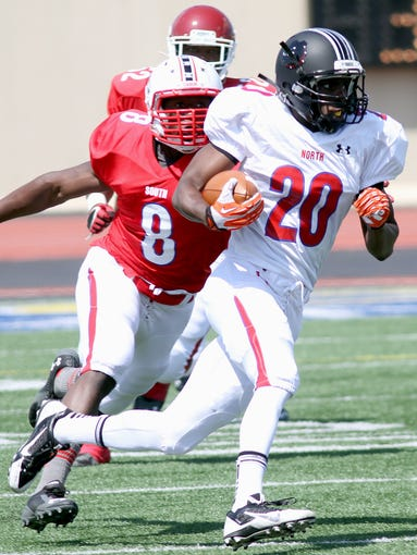 Tegray Scales, 8, from Colerain, chases down Marcus Whitfield, 20, from Mass. Washington during the Ohio North-South Classic at Welcome Stadium in Dayton.