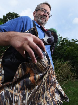 Matt Schmitt demonstrates his DuckPockets, a vest-like carrying bag for duck decoys. Schmitt and his invention recently won the Muskingum County Business Incubator's Startup Weekend