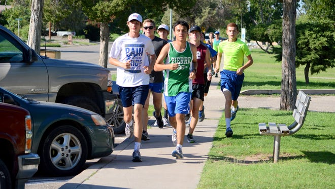 Members of the Cavemen cross country team continue their training Tuesday at Lake Carlsbad Beach Park. Carlsbad will host the Ron Singleton Invitational on Saturday.