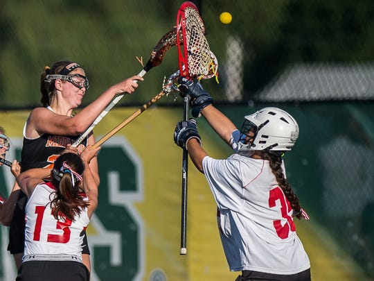 Middlebury's Anna Hodson, left, gets a shot over CVU's Ali Weiner to score during their girls lacrosse championship battle at Virtue Field at UVM on Friday night, June 8, 2018.