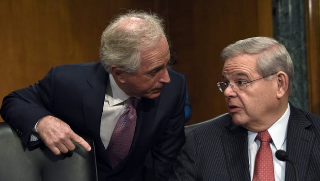 Sen. Robert Menendez, D-N.J., right, and Sen. Bob Corker, R-Tenn. chairman of the Senate Foreign Relations Committee, talk on Capitol Hill in Washington on Jan. 27, 2015.