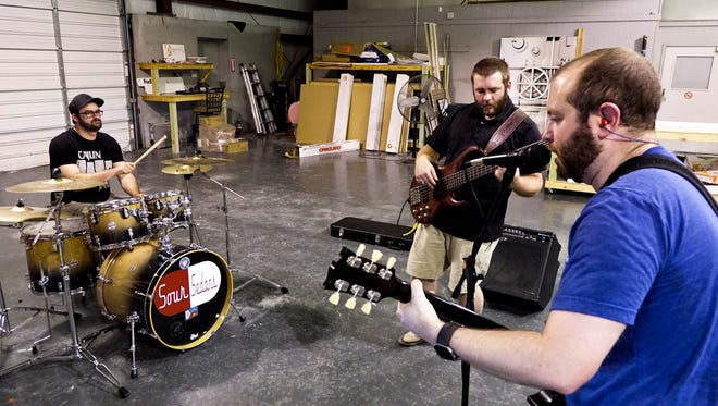 Ryan Cazares, right, an optometrist from Scott, plays lead guitar and vocals during Dr. C. and the Gris Gris' rehearsal at a print shop in Broussard Tuesday, July 18, 2017.